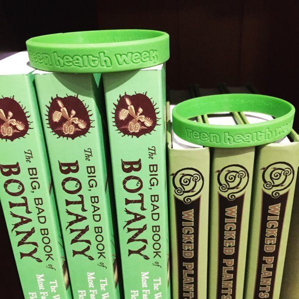 "Green ""Teen Health Week"" wristbands on display atop several Mütter Museum store books."