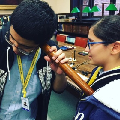 Two students from the Karabots Junior Fellows Program experiment with a Laënnec stethoscope