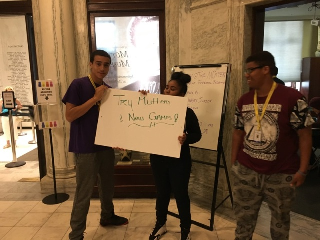 "Several of the Karabots Junior Fellows entice visitors to the Müttre Museum to try their games, holding a sign saying ""Try Mütter's New Games"""