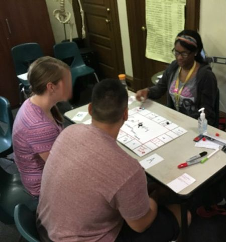 A student in the Karabots Junior Fellows Program demonstrates a board game on forensics to two visitors to the Mütter Museum