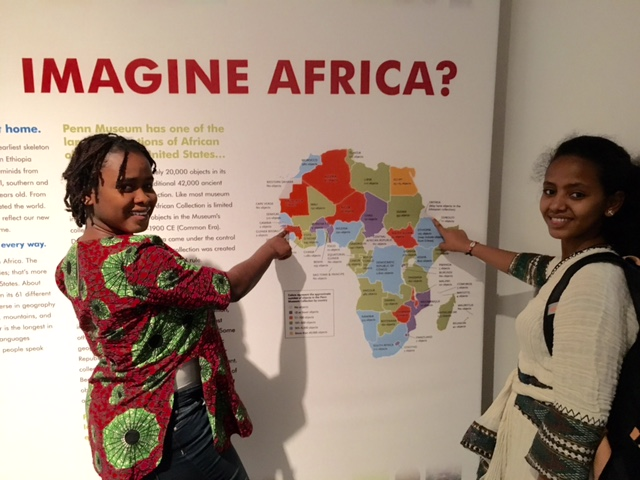 "Binta and Adunia, two students from the Teva Pharmaceuticals Internship Program, pose in front of the main label for the Penn Museum's ""Imagine Africa"" exhibit"