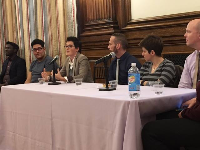A speaker talks into a microphone at an Out4STEM panel discussion. Other panelists stand behind a table.