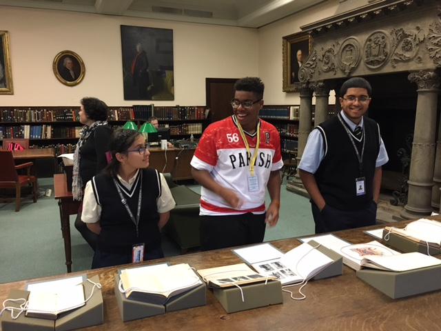 Three students from the Karabots Junior Fellows program stand in front of books on display in the Historical Medical Library for the Banned Books Week exhibit