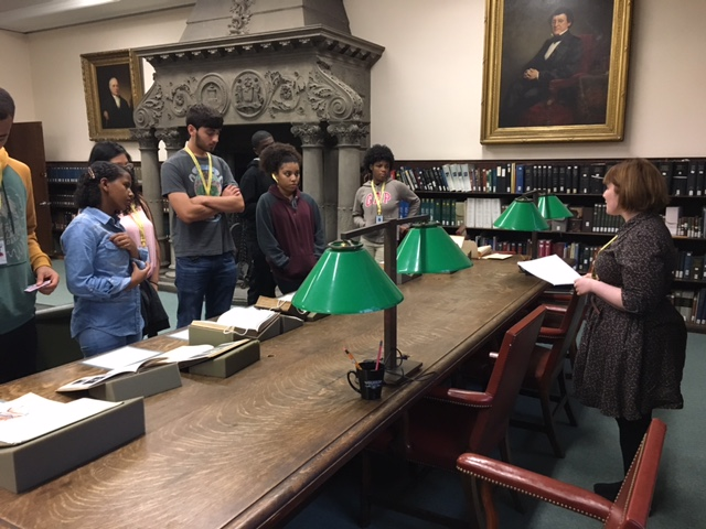 Students from the Teva Pharmaceuticals Internship Program stand in front of books on display for the Historical medical Library's exhibit for Banned Books Week. They are speaking with Library Assistant Caitlin Angelone.