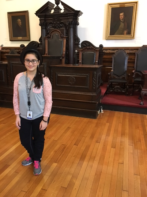 Photo of Viviana, a student in the Karabots Junior Fellows Program, who is wearing a top hat to commemorate her victory in the Project Voice 2016 election.