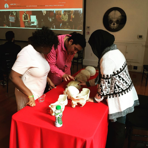 Sara, a student in the Karabots Junior Fellows Program, teaches two students about skull pathology by displaying a group of human skull replicas at World AIDS Day 2016