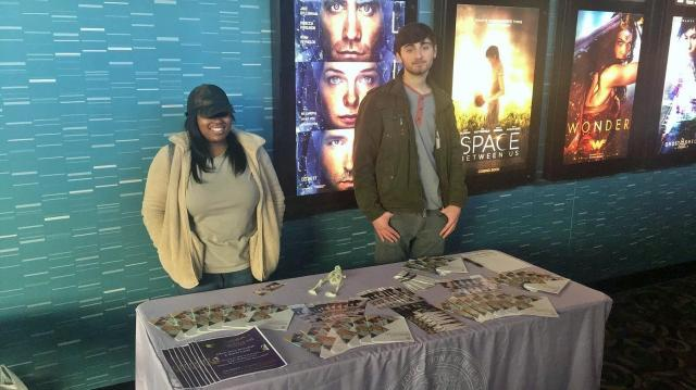 Students from the Teva and Out4STEM Programs stand at a table covered in literature about CEPI programming at Rave Cinemas at University City