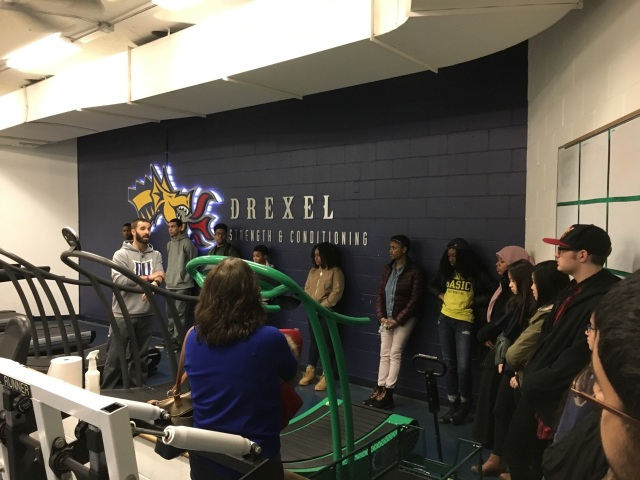 Students in the Karabots Junior Fellows Program talk with Michael Rankin, director of strength and conditioning at Drexel University. They stand in the midst of various exercise equipment (a treadmill is in the center frame).