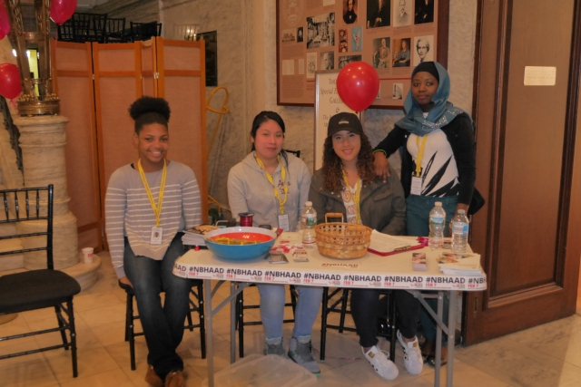 Four students in the Teva Pharmaceuticals Internship Program stand behind a registration table at National Black HIV/AIDS Awareness Day