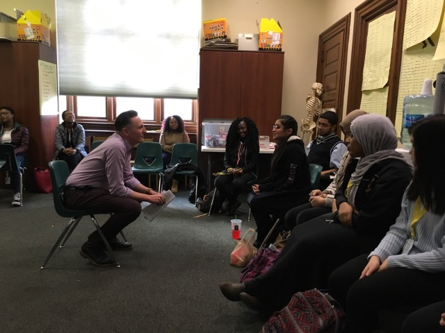 Jon Goff, Associate Director of Fellow Ship Relations for the College of Physicians of Philadelphia, conducts a mock job interview with Viviana, a student in the Karabots Junior Fellows Program. The two are seated opposite each other (Goff to the left, Viviana to the right). Several other students are seated in the foreground and background.