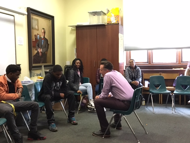 Jon Goff, Associate Director of Fellow Ship Relations for the College of Physicians of Philadelphia, conducts a mock job interview with Quran, a student in the Karabots Junior Fellows Program. The two are seated opposite each other (Goff in the center, and Quran to the left). Several other students are seated in the foreground and background.