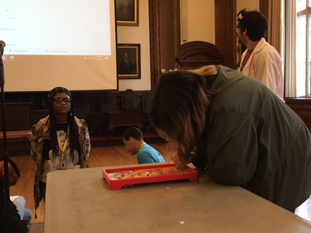 A student in the Karabots Junior Fellows Program leans over a game of Operation while another student looks on. Part of a game show activity.
