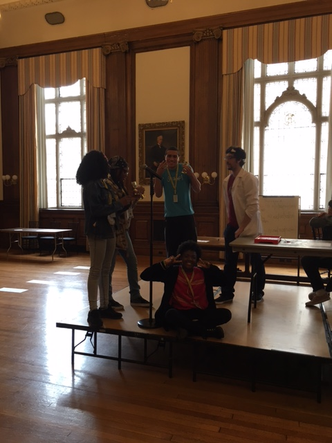 Students in the KArabots Junior Fellows Program stand on a stage in Mitchell Hall at the College of physicians of Philadlephia. They receive small trophies for competing in an educational game show.