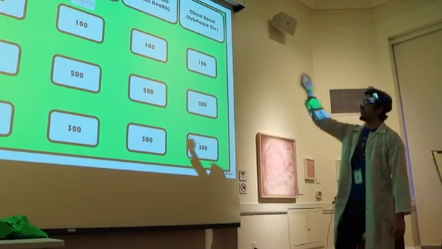 "Youth Program Coordinator Kevin Impellizer (dressed in a lab coat and goggles) gestures to a projection screen, on which a Jeopardy-style game board is projected. The game took place at the ""Friday the 13th @ the Mütter"" event at the College of Physicians of Philadlephia"