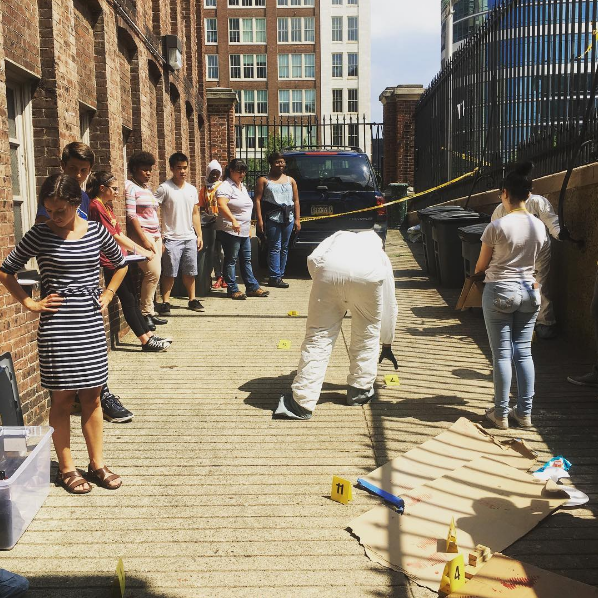 Students in the Teva Pharmaceuticals Internship Program investigate a mock crime scene at the loading dock behind the College of Physicians of Philadelphia