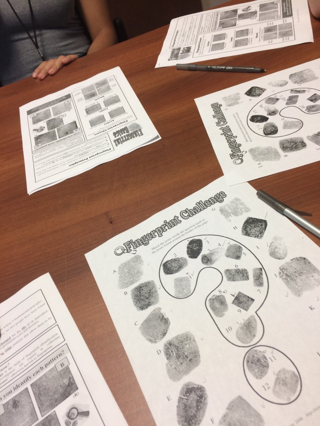Sheets of fingerprints collected at the Arcadia Crime Scene House are spread across a table.