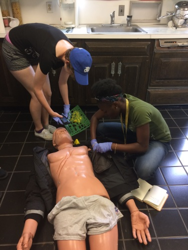 Students from the Center for Education's youth programs gather evidence from a human dummy simulating a victim at the Arcadia Crime Scene House