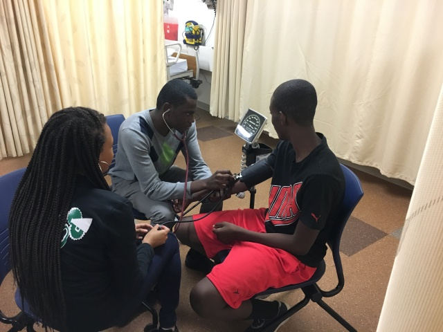 Students in the KArabots Junior Fellows Program monitor each other's blood pressure at Drexel University's Physical Therapy Lab