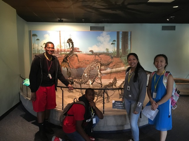 Students in the Karabots Junior Fellows Program pose in front of a dinosaur display at the Academy of Natural Sciences