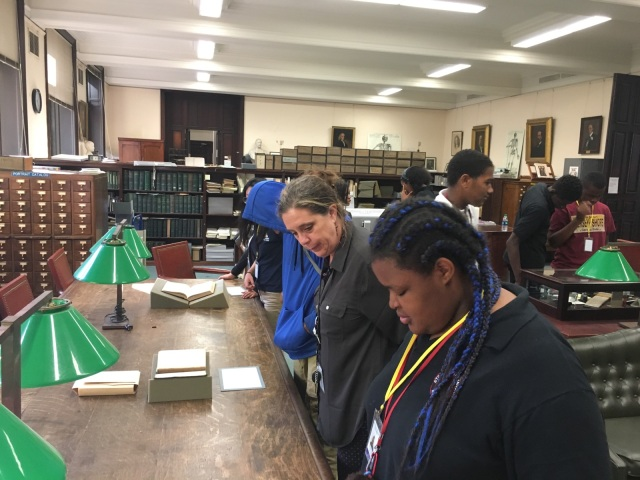 Students in the Karabots Junior Fellows Program examine a set of challenged books on display at the Historical Medical Library