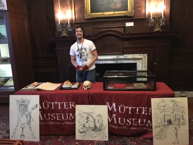Youth Program Coordinator Kevin Impellizeri stands behind a table of specimens and books related to syphilis for a lesson at the Mütter Museum