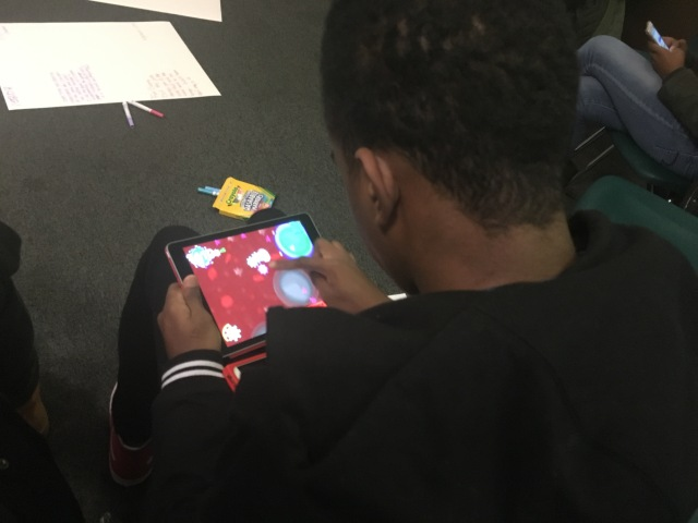 A student in the Karabots Junior Fellows Program plays CD4 Hunter, a mobile game about how HIV infects a healthy cell, on an iPad