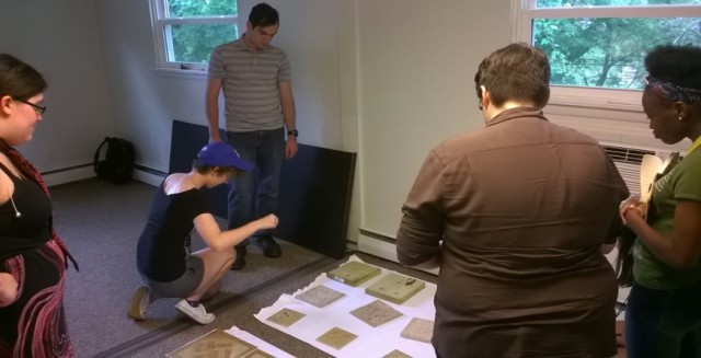 Students in the OUt4STEM internship program examine plaster molds of footprint impressions during a lesson on crime scene investigation at Arcadia University