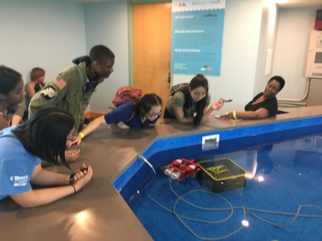 Students in the Karabots Junior Fellows Program pilot a small submarine in a pool in the lobby of the Independence Seaport Museum
