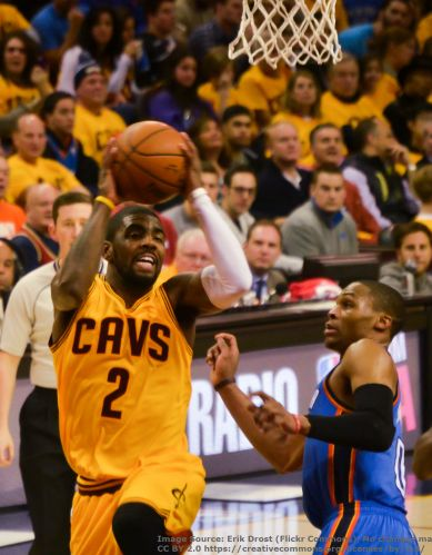 Cleveland Cavaliers point guard Kyrie Irving goes for a layup against a defender.