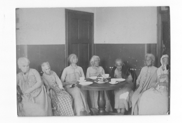 "Seven female patients in the ""Insane Department"" at Philadelphia General Hospital sit around a small table."