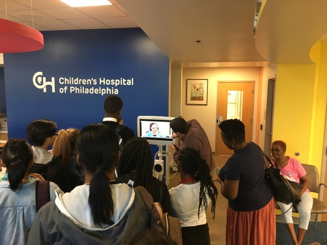 Students in the Karabots Junior Fellows Program interact with a medical interpreter on a scree at the CHOP Karabots Pediatric Care Center