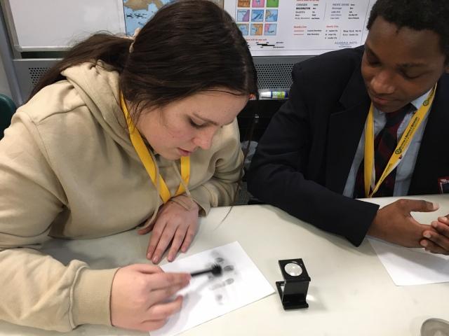 Two students in the Karabots Junior Fellows Program examine fingerprints