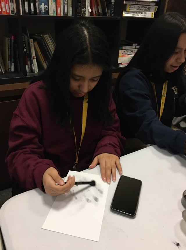 A student in the Karabots Junior Fellows Program dusts for fingerprints
