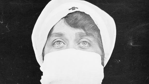 A nurse with a mask over her face.