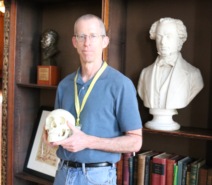 Photograph of Mütter Museum docent Joe Walsh holding a skull next to a bust of Thomas Dent Mütter