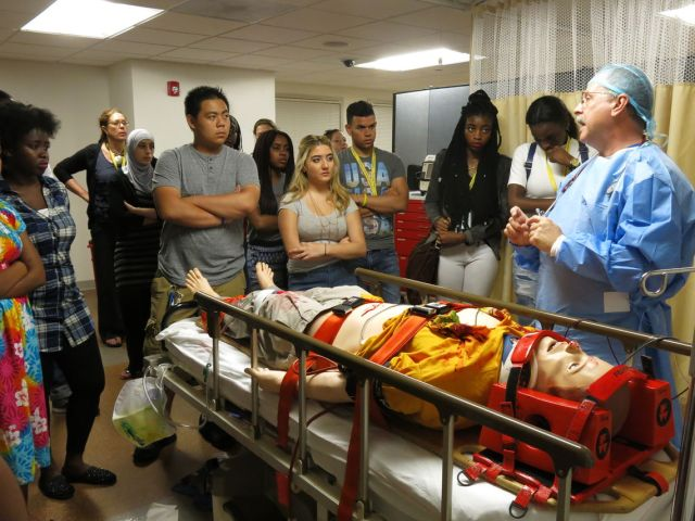 Students stand around a gurney holding a medical dummy. A doctor in scrubs addresses the students.