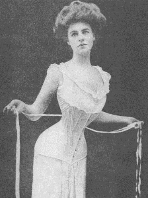 A young white woman. She wears a frilly, sleeveless dress with a corset along her midsection. She holds tailor's tape along a very thin waist.