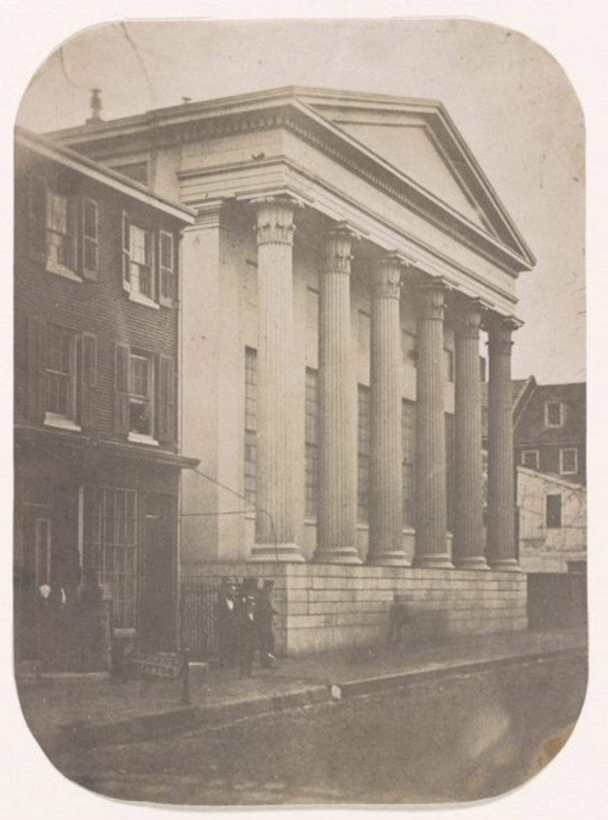 Street view of a white marble building with Greek columns